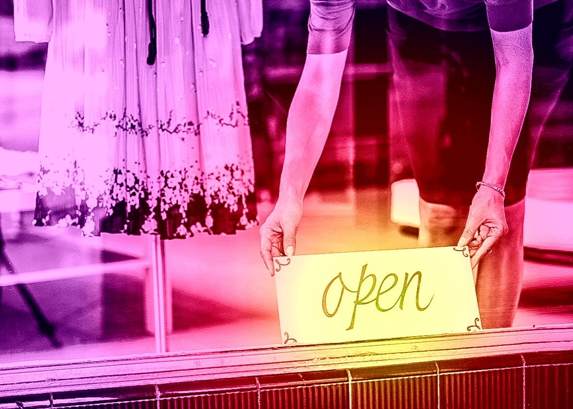 Boutique salesperson placing open sign on window.