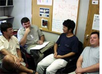 Students Alexei, Nate, Jian, and post-doc Eric discuss the plan