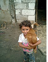 A Roma child holds a dog
