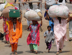Women carrying parcels on their heads. Click image to expand.