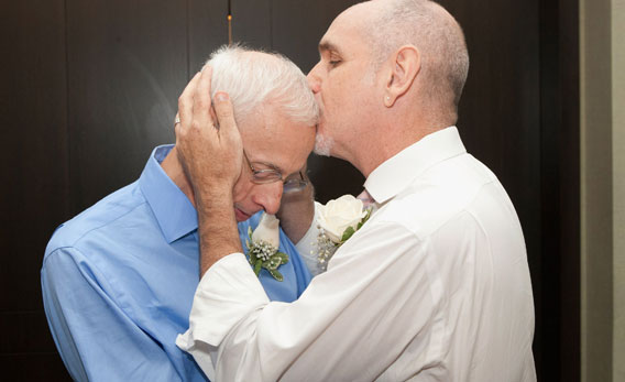 Same-sex couple Frank Faria and Randy Faria (R) kiss as they wed during the first day of legal same-sex marriage in New York State on July 24, 2011 in New York City.