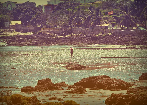 A man walks along the beach during low tide in Conakry, Guinea