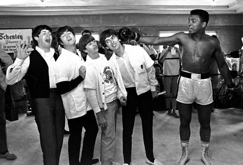 The Beatles, from left, Paul McCartney, John Lennon, Ringo Starr, and George Harrison, take a fake blow from Cassius Clay, who later changed his name to Muhammad Ali.