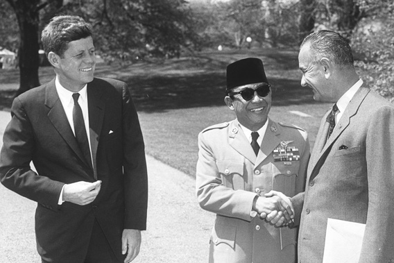 President of Indonesia Sukarno (center) shakes hands with US Vice President Lyndon Johnson as President John F. Kennedy smiles.