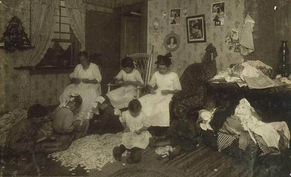 Stringing buttons from button molds in a crowded Massachusetts home, September 1912.