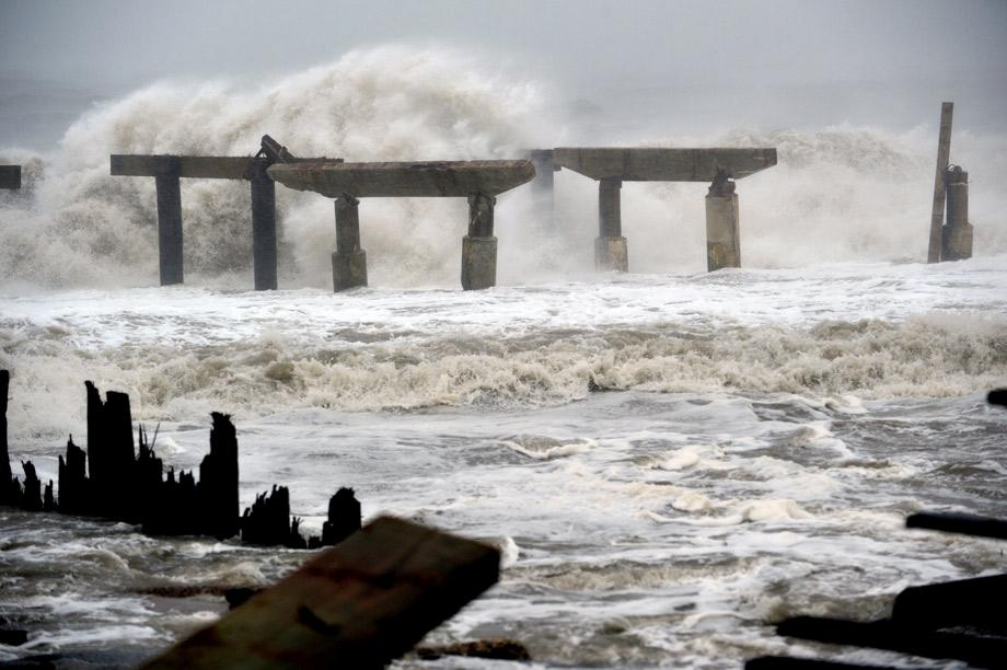 Waves crash against a previously damaged pier before landfall of Hurricane Sandy on Monday in Atlantic City, New Jersey.