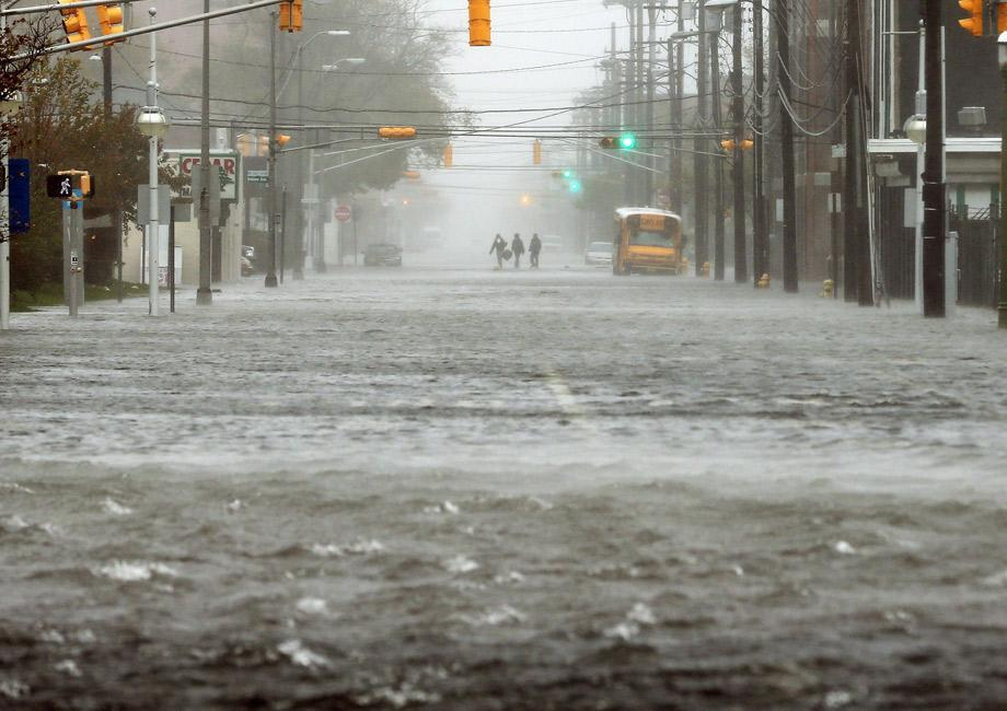 People walk down a flooded street as Hurricane Sandy moves up the coast on Monday in Atlantic City, New Jersey.