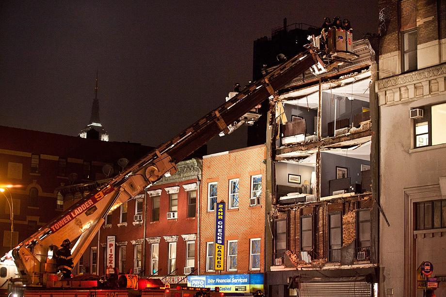 Fire fighters evaluate the scene of an apartment building which had the front wall collapse due to Hurricane Sandy on October 29, 2012 in New York.