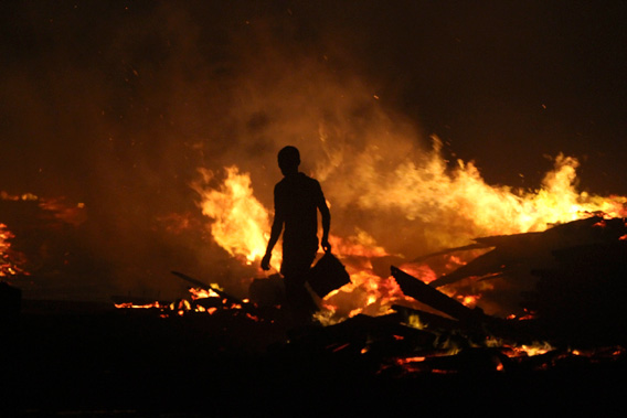 A man holds a bucket as he tries to extinguish a late night fire at the Okobaba sawmill near the Lagos Lagoon January 8, 2013.