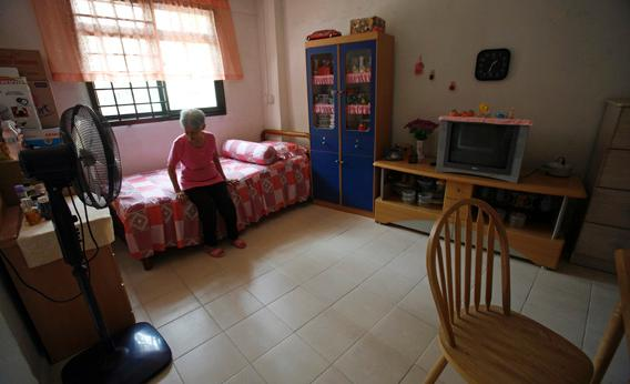 Emily Low, 78, sits on a bed in the combined living room and bedroom of her one-room Housing Development Board flat in Singapore November 2, 2007.