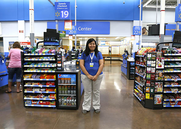 A cashier waits for customers at a Walmart Supercenter in Rogers, Arkansas June 6, 2013.