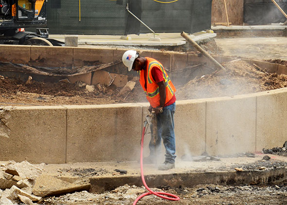 A worker at a construction site in Rockville, Maryland, breaks up concrete with a jackhammer, creating a cloud of silica dust.