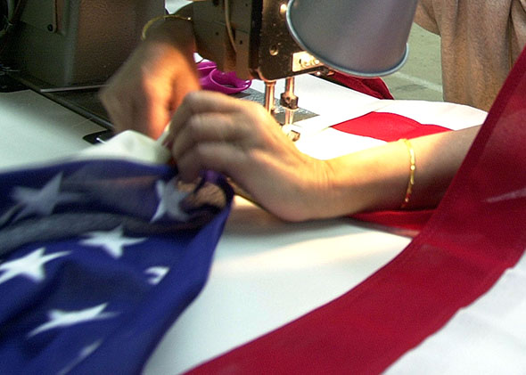 A woman adjusts her sewing machine as she sews an American flag