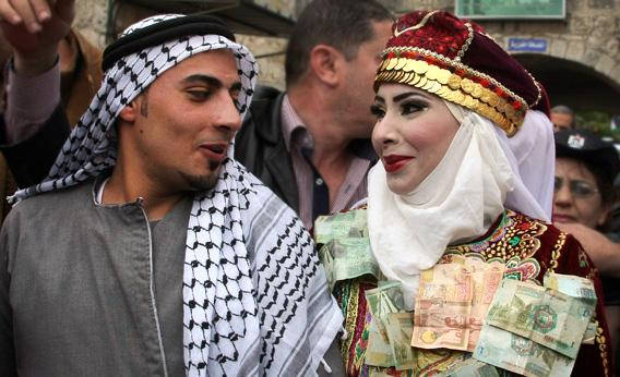 The Palestinian bride and groom Mhaha Salam, right, and Thayer Qasem, left, walk down the street on their wedding day.