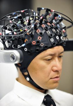 A man wears a brain-machine interface, equipped with electroencephalography (EEG) devices and near-infrared spectroscope (NIRS) optical sensors in a special headgear to measure slight electrical current and blood flow change occuring in the brain.