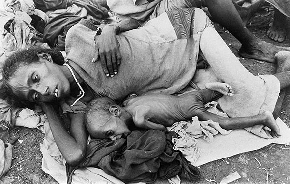 A starving mother and a child wait for food at a relief camp in the province of Wollo, Ethiopia, during a widespread famine in December 1984.