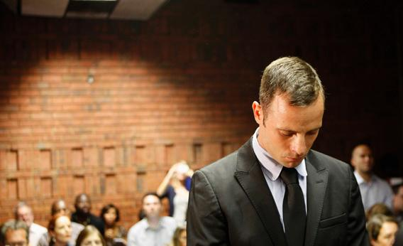 Oscar Pistorius stands in the dock during a break in court proceedings at the Pretoria Magistrates court, Feb. 20, 2013.
