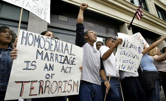 Demonstrators hold sign reading, 'homosexual marriage is an act of terrorism' as they chant slogans against same-sex marriages.