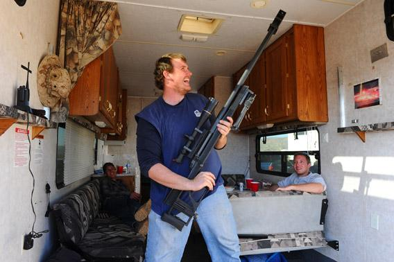 During a break in his trailer, Randall Bymoen  shows off his gun at the Big Sandy Machine Gun Shoot in March.