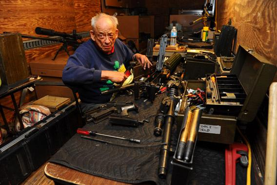 Machine-gun guru Dolf Goldsmith repairs a machine gun in his mobile shop at the Big Sandy Machine Gun Shoot in March.