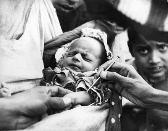 A baby is vaccinated against smallpox at an emergency clinic in Karachi during the worst epidemic of smallpox in Pakistan's history, January 1962.