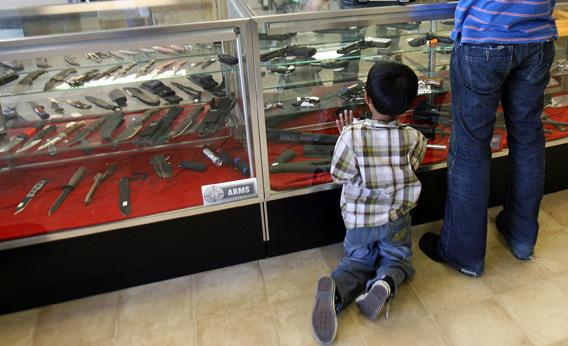 A boy looks at guns in a case.
