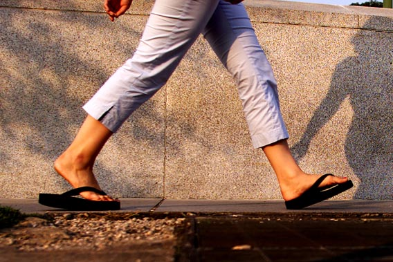 A woman walks with flip flops in Washington, July 15, 2003.