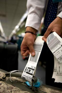 Man showing his baggage tags from Mexicana Airlines to Mexico City.