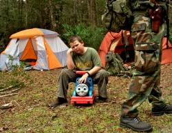 A young boy sits on a child's toy and sulks because his sister got to carry the rifle that he wanted to carry as members of the North Florida Survival Group gather for a field training exercise in Old Town, Florida, December 8, 2012.