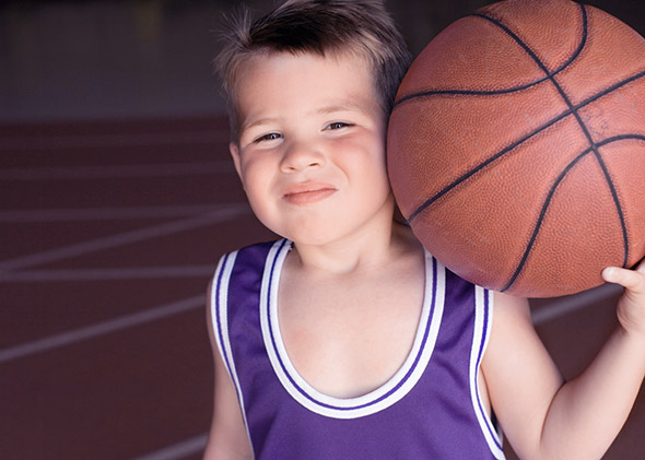 Boy in basketball uniform holding basketball.