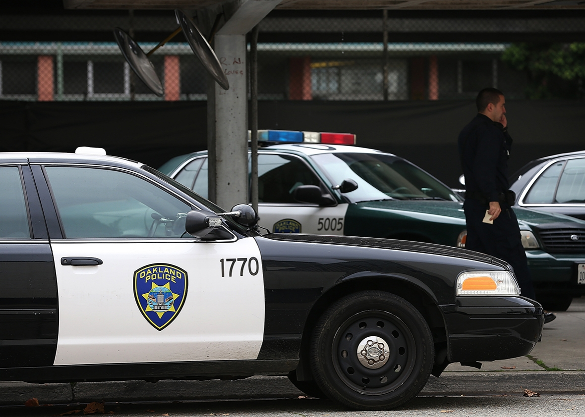 An Oakland Police officer walks by patrol cars at the Oakland Police headquarters on December 6, 2012 in Oakland, California.