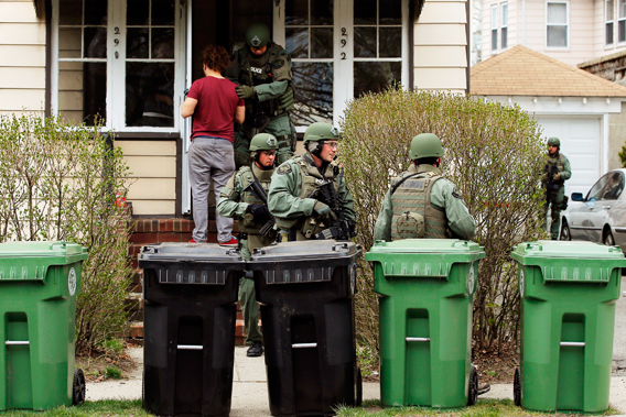 Residents watch as police officers search house to house for the second suspect in the Boston Marathon bombings in a neighborhood of Watertown, Massachusetts April 19, 2013.