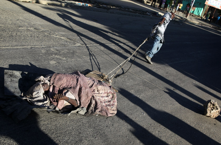 A man drags a dead cholera victim through the streets of Cap-Haitien on Nov. 19, 2010, after four days of riots between demonstrators and U.N. peacekeepers accused of bringing cholera to the country. Preparations for key upcoming elections pressed ahead despite violent clashes with U.N. troops blamed by Haitians for importing a cholera epidemic that has now claimed nearly 1,200 lives.