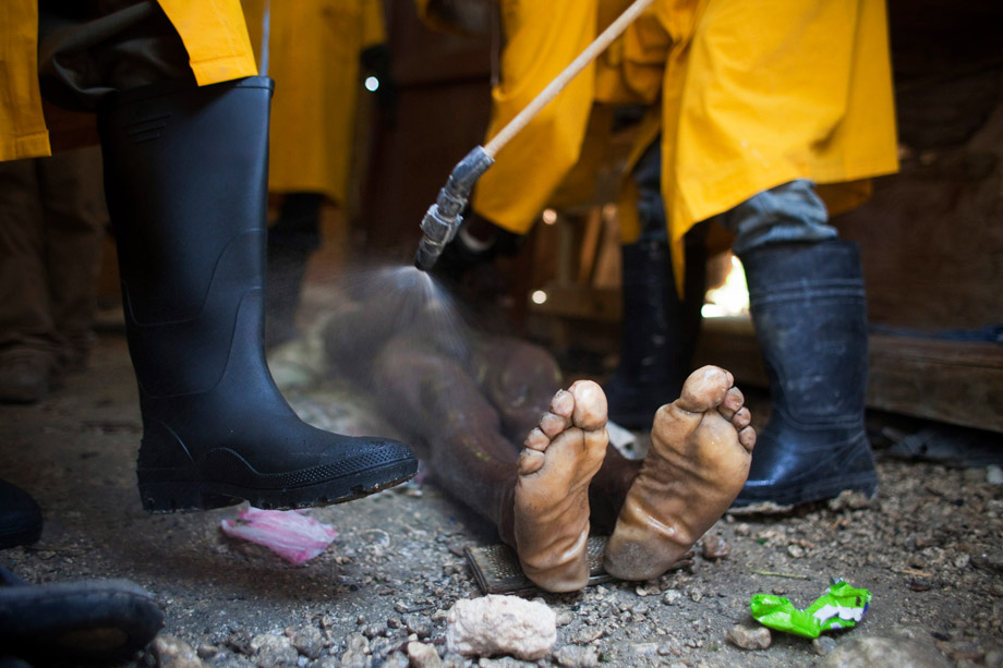 Members of a Haitian Ministry of Health body-collection team spray a mixture of bleach and water to disinfect the body of Nixon Merise, 24, who died of cholera, before removing his body from his home in the Carrefour neighborhood of Port-au-Prince, Nov. 20, 2010.