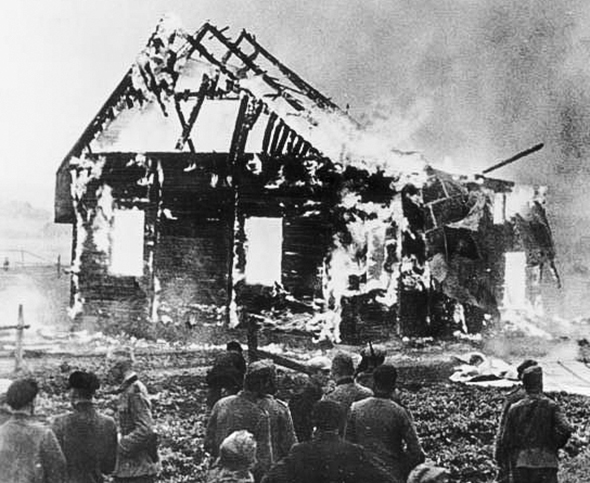 Nazi officers and Lithuanian locals look on as a synagogue burns