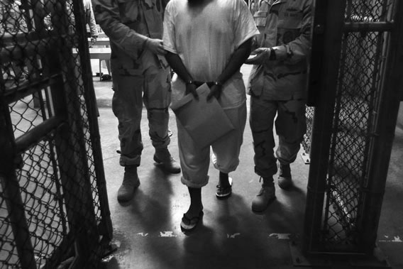 "U.S. Navy guards escort a detainee after a ""life skills"" class held for prisoners at Camp 6 in the Guantanamo Bay detention center on March 30, 2010 in Guantanamo Bay, Cuba."