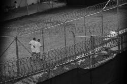 Detainees jog inside a recreation yard at Camp 6 in the Guantanamo Bay detention center on March 30, 2010 in Guantanamo Bay, Cuba.