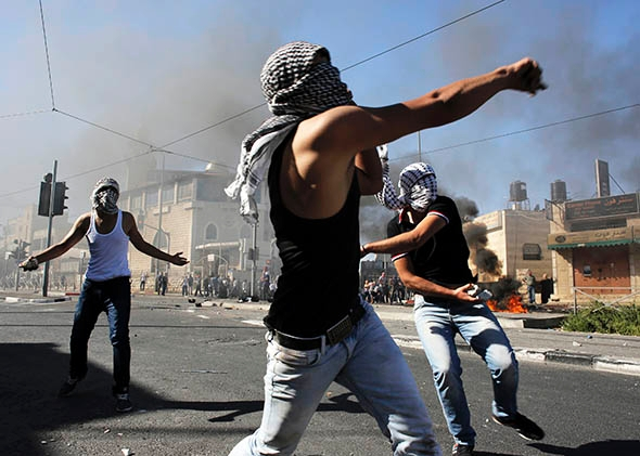 Palestinians hurl stones during clashes with Israeli police in Shuafat, an Arab suburb of Jerusalem, on July 2, 2014.