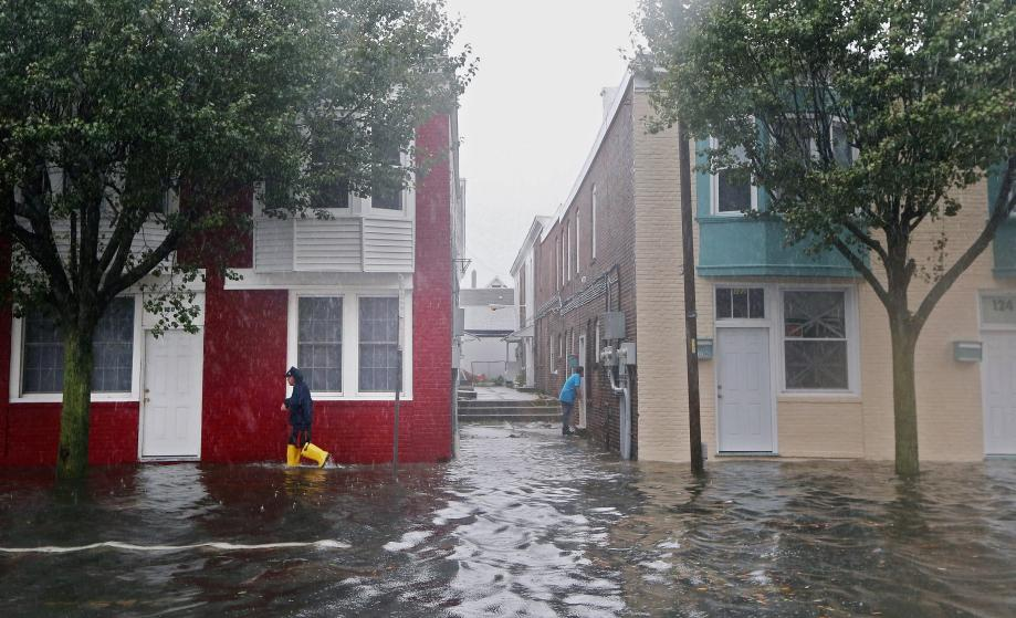 A man walks down a flooded street ahead of Hurricane Sandy on Monday in Atlantic City, New Jersey.