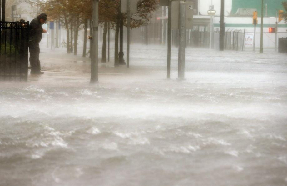 A man stands on a dry patch of sidewalk on a flooded street as Hurricane Sandy moves up the coast on Monday in Atlantic City, New Jersey.