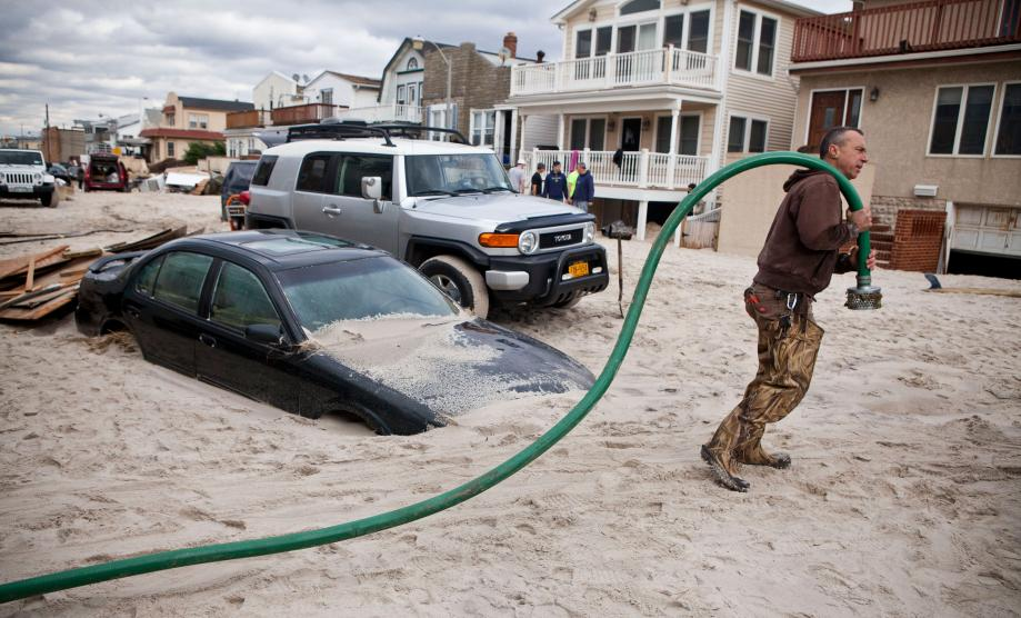Robert Justh drags a hose while attempting to drain a flooded basement, caused by Hurricane Sandy, on October 31, 2012 in Long Beach, New York.