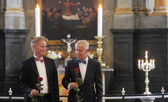 Stig Ellins, left, and his partner Steen Andersen pose with a rose after their wedding at Frederiksberg church in Copenhagen in June.