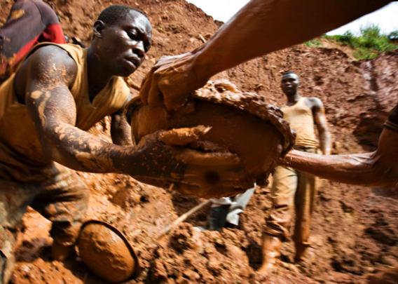 Gold miners in northeastern Congo form a human chain while digging an open pit.