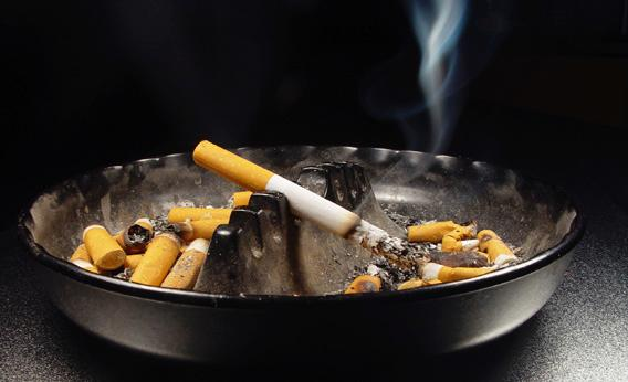 A cigarette burning in an ashtray.