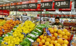 Sales associate Leo De La Cruz restocks fresh fruit during the Grand Opening of the new Walmart Neighborhood Market in Panorama City, California, a working class area about 13 miles (20km) northwest of Los Angeles, on September 28, 2012.