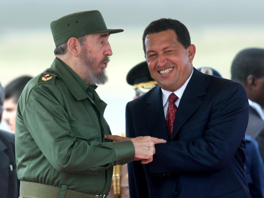 Fidel Castro (L) and Hugo Chavez joke after Castro's arrival at Caracas' Maiquetia airport, October 26, 2000. Castro is in Venezuela for a five day state visit during which he will sign an agreement to purchase subsized oil from Venezuela.  AW - RTR9ZZX
