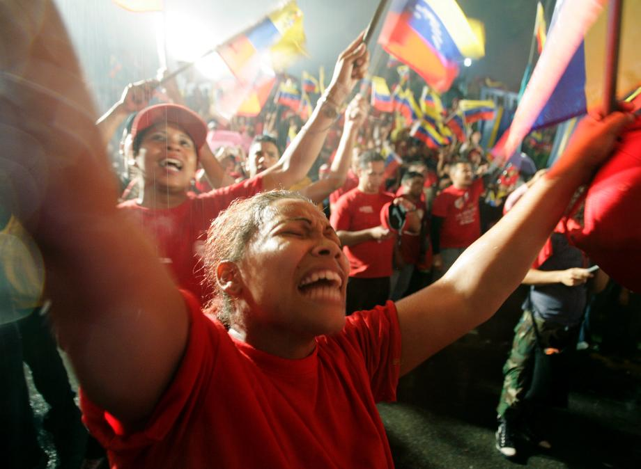 "Supporters of Venezuelan President Hugo Chavez celebrate in the rain in front of the Miraflores Palace as Chavez gives a speech from the balcony after official election results gave him a victory by a wide margin in Caracas December 3, 2006. The anti-U.S. Venezuelan president claimed victory with a cry of ""long live the revolution"" as official results showed him heading for a landslide re-election win on Sunday."