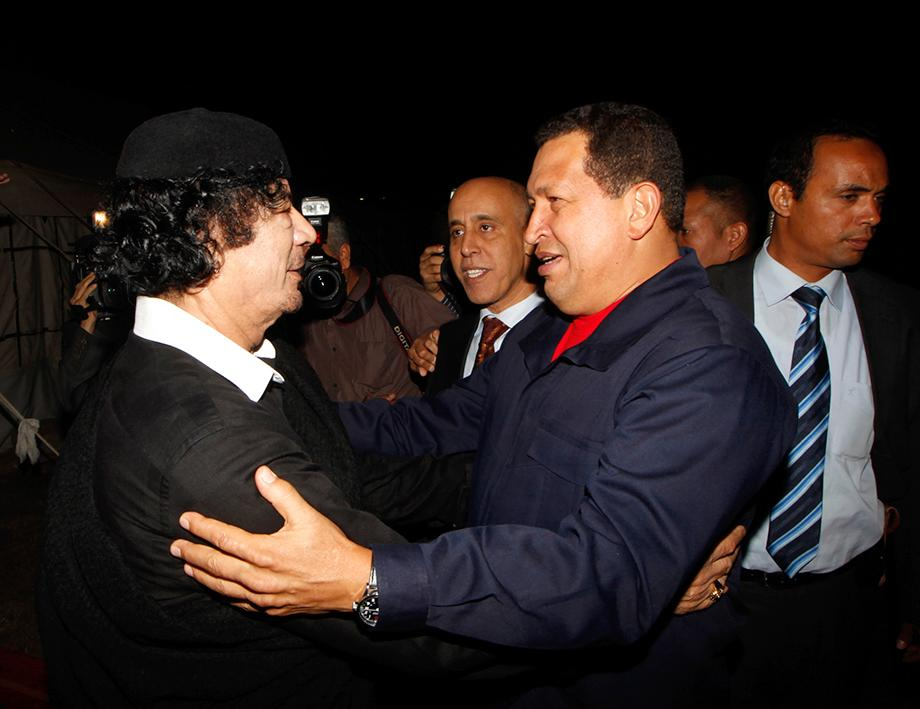 Libyan leader Moamer Kadhafi  (L)  welcomes Venezuelan President Hugo Chavez (R) upon his arrival in Tripoli on October 22, 2010. Chavez arrived in Libya for talks with the country's leader Moamer Kadhafi, on a regional tour that has also taken him to Iran and Syria. The firebrand president's programme has not been made public, but he arrived from Damascus and was to begin his visit by meeting Kadhafi, with whom he has had close ties for several years. AFP PHOTO MAHMUD TURKIA