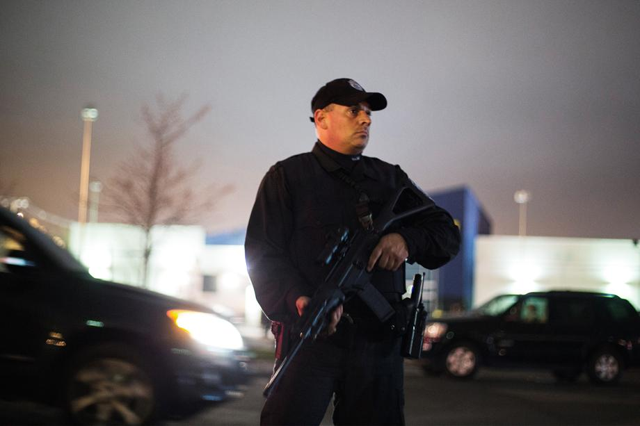 A law enforcement official stands with his rifle during a search for the two men suspected of setting off two explosions during the Boston Marathon in Watertown, Massachusetts, April 19, 2013. Massachusetts State Police warned people in the Boston suburb of Watertown not to open their doors and said they would conduct a door-to-door, street-by-street search due to what it called a fluid situation.