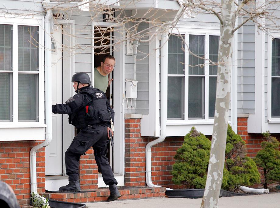 "A man looks out of his door as a SWAT team member knocks on his neighbors door as they search for the remaining suspect in the Boston Marathon bombings in Watertown, Massachusetts April 19, 2013. Boston Police Commissioner Ed Davis warned the entire city of Boston to ""shelter-in-place"" on Friday as authorities pressed a manhunt for the second suspect in the Boston Marathon bombings."